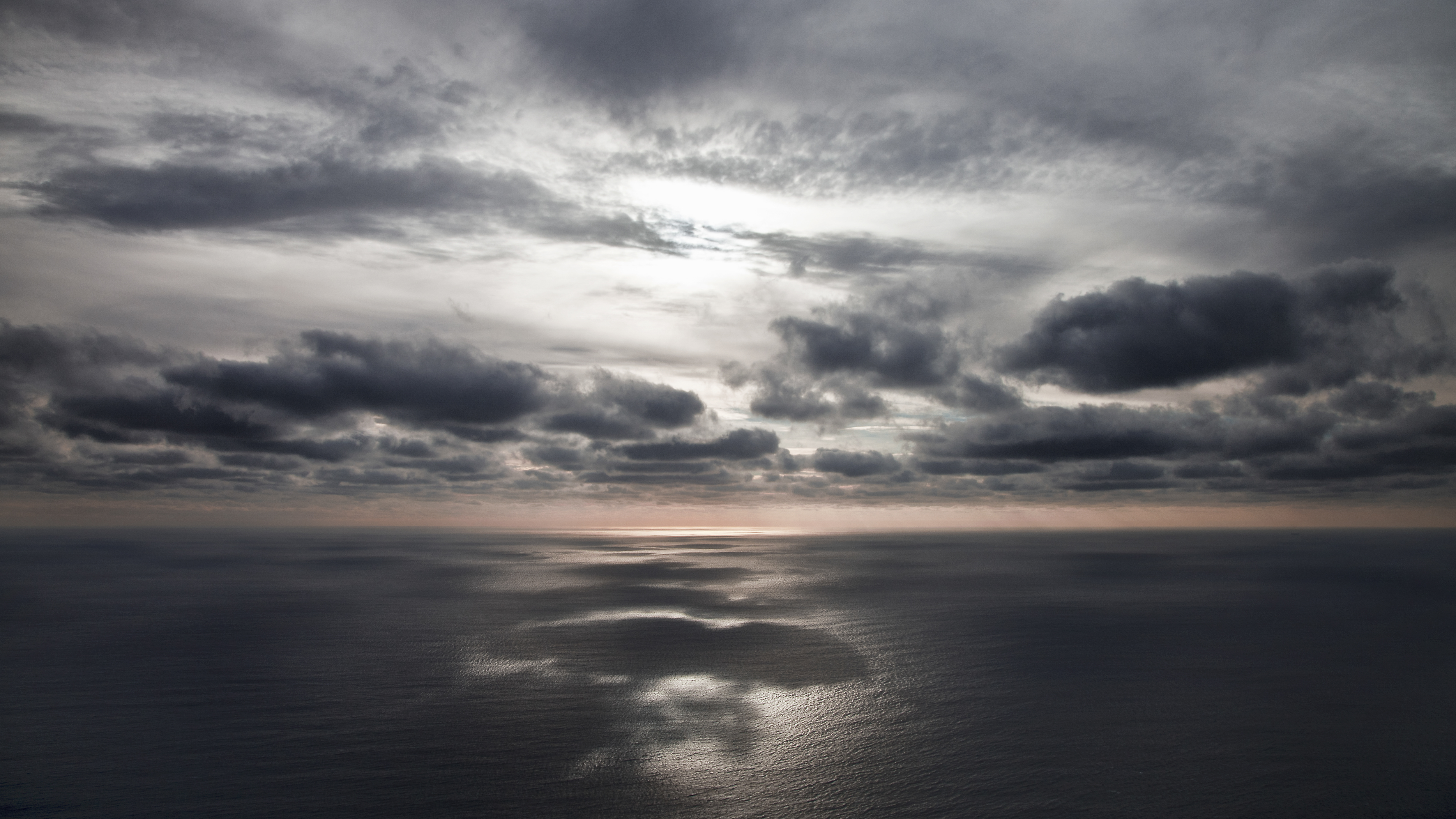 A distant sunset ocean horizon, dark clouds reflecting on the sea.